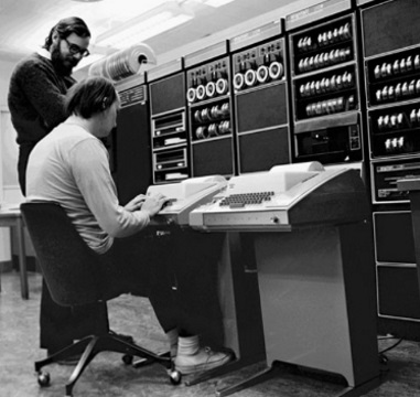 Ken Thompson and Dennis Richie (standing) working on a DEC PDP-11 via teletype (notice no electronic display)